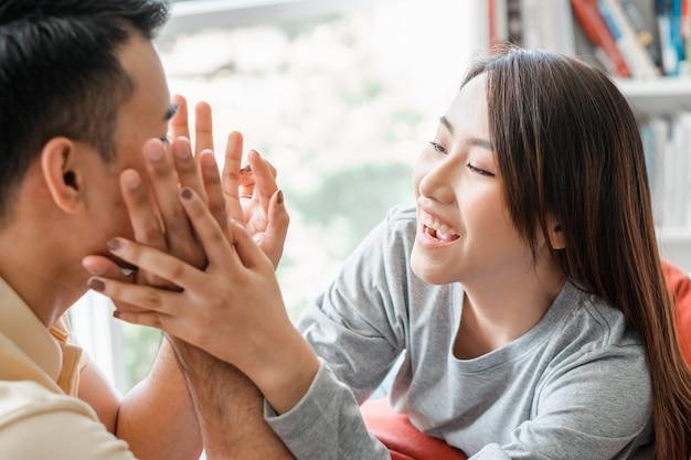 Gelukkige paar zittend op de bank en een man zijn plaagt zijn vriendin met liefde in de woonkamer