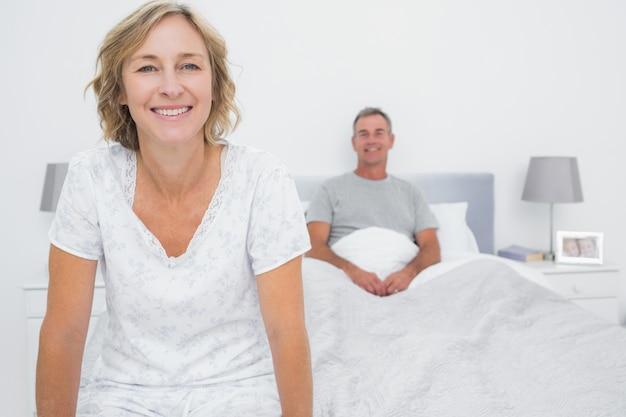 Gelukkige paar zittend op de tegenovergestelde uiteinden van bed