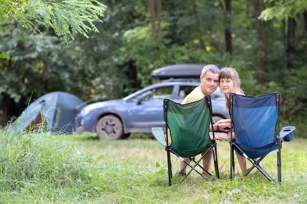 Gelukkige paar zittend op stoelen op de camping samen ontspannen.