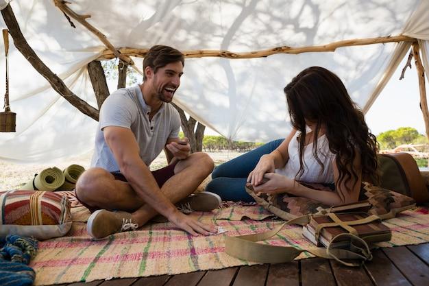Gelukkige paarspeelkaarten in tent
