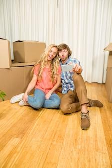 Gelukkige paarzitting op de vloer die selfie in hun nieuw huis nemen