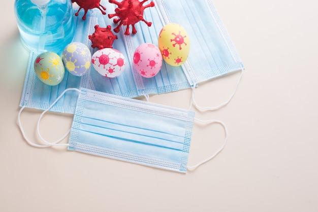 Gelukkige paasdag eieren en coronavirus (covid-19) heeft chirurgische maskers alcohol gel op papier achtergrond met kopie ruimte.