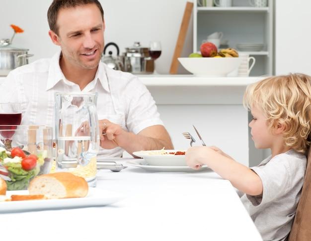 Gelukkige papa die zijn zoon bekijkt die deegwaren eet