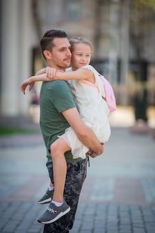 Gelukkige papa en klein aanbiddelijk meisje in de stad in openlucht