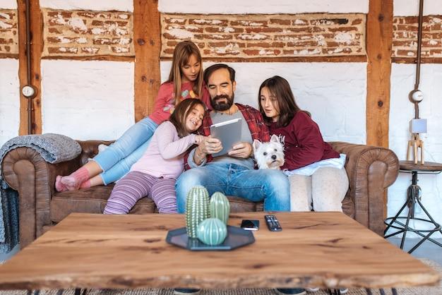 Gelukkige papa met zijn dochters die op de tablet kijken die thuis in de bank met de hond zitten