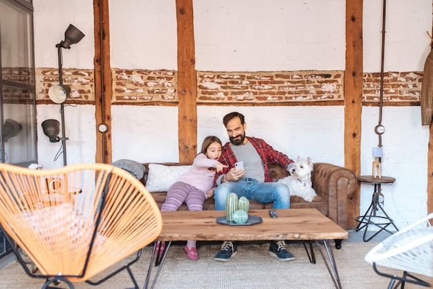 Gelukkige papa met zijn kleine dochter die op de telefoon kijken die thuis in de bank met de hond zitten