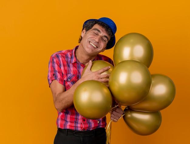 Gelukkige partijman van middelbare leeftijd die partijhoed draagt die ballons met gesloten ogen houdt die op oranje muur met exemplaarruimte worden geïsoleerd