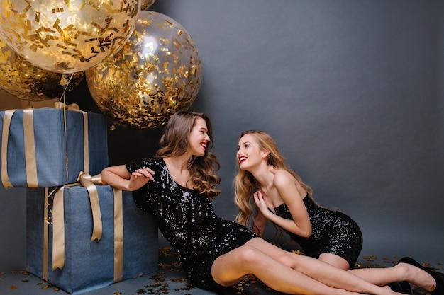 Gelukkige partijmomenten twee aantrekkelijke jonge vrouwen die op vloer dichtbij grote cadeautjes koelen. luxe jurken, lang krullend haar, positiviteit uitdrukken, geweldige feesten, vrienden, geluk.