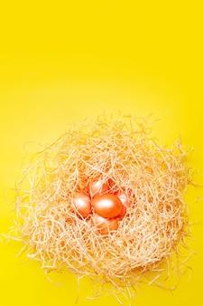 Gelukkige pasen-achtergrond, gekleurde roze en oranje eieren in hooinest over heldere gele kleur