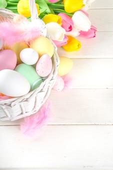 Gelukkige pasen-achtergrond met kleurrijke eieren in mand en lentebloemen. pasen lente holidat wenskaart achtergrond