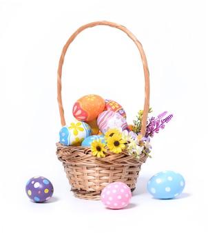 Gelukkige pasen-dag kleurrijke eieren in mand met bloemen die op witte achtergrond worden geïsoleerd.