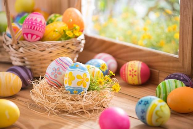 Gelukkige pasen-dag kleurrijke eieren in nest en bloem op hout met vensterverlichting