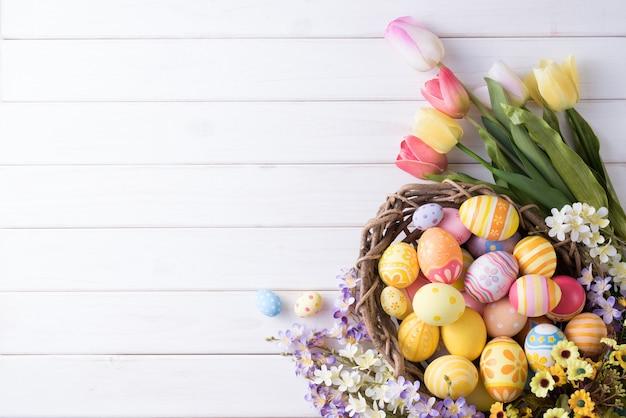 Gelukkige pasen-dag kleurrijke eieren in nest en bloemdecoratie op wit hout