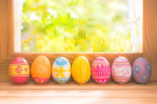 Gelukkige pasen-dag kleurrijke eieren op hout bij vensterverlichting met exemplaarruimte