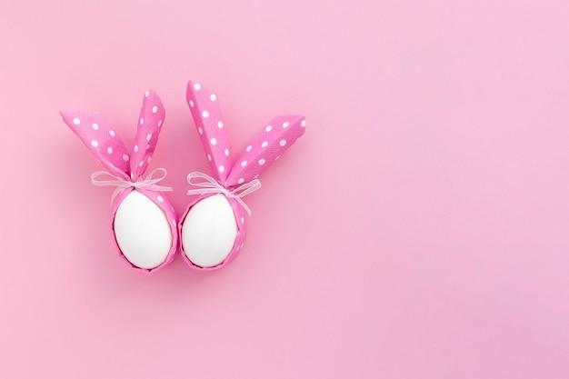 Gelukkige pasen feestelijke achtergrond. twee paaseieren met konijnenoren op roze met exemplaarruimte.