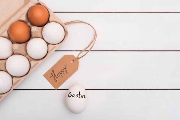 Gelukkige pasen-inschrijving met eieren in rek