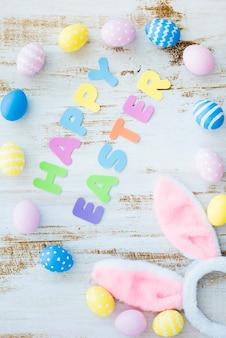 Gelukkige pasen-inscriptie met gekleurde eieren en konijntjesoren