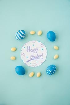 Gelukkige pasen-inscriptie op papier met gekleurde eieren