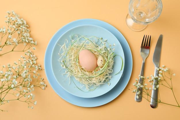Gelukkige pasen-lijst die met eieren op beige achtergrond plaatst