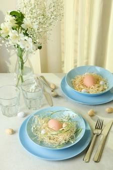 Gelukkige pasen-lijst die met eieren op witte geweven lijst plaatst