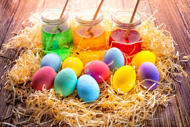 Gelukkige pasen met kleurrijke eieren in stro. tafel versieren voor vakantie. bovenaanzicht