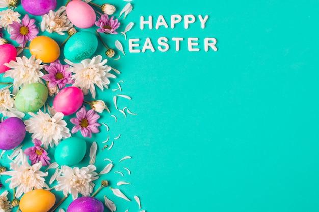 Gelukkige pasen-titel dichtbij heldere eieren en bloemknoppen