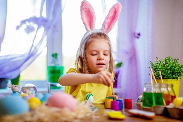 Gelukkige pasen-vrouw die in konijntjesoren eieren, klein kind thuis schilderen. lente vakantie