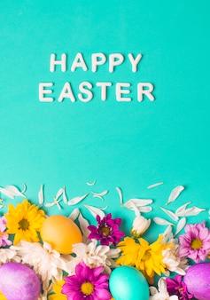 Gelukkige pasen-woorden dichtbij heldere eieren en bloemknoppen