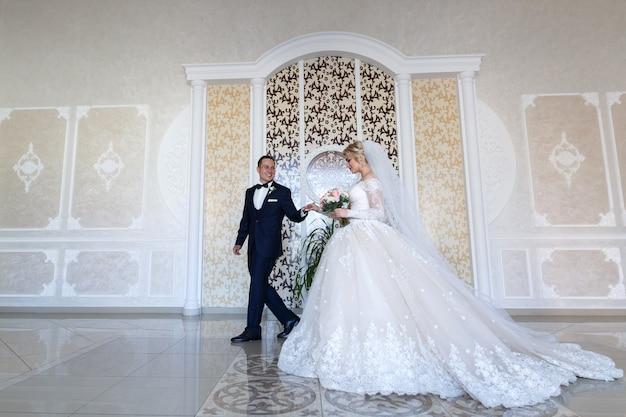 Gelukkige pasgetrouwden kijken elkaar zacht aan. lachende bruid en bruidegom zachtjes knuffelen binnenshuis in de witte kamer. bruidspaar in een huwelijksceremonie in een stijlvol interieur. wieden dag