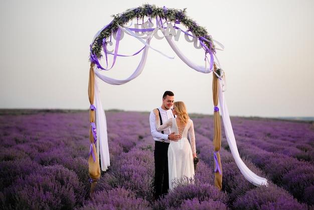 Gelukkige pasgetrouwden staan bij zonsondergang in de buurt van de ceremoniële boog in een bloeiend lavendelveld