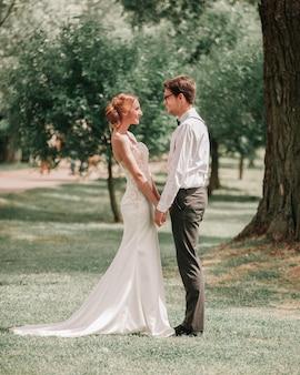 Gelukkige pasgetrouwden staan samen in een zonnig park.