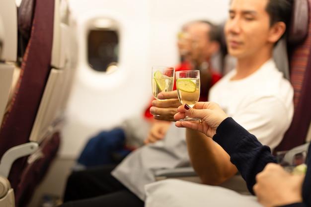 Gelukkige passagiers die glasalcohol in de vliegtuigviering roosteren op vakantie.