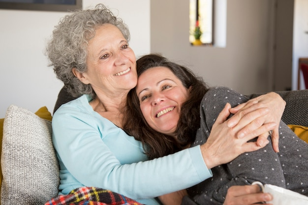 Gelukkige peinzende hogere dame die haar dochter thuis omhelst