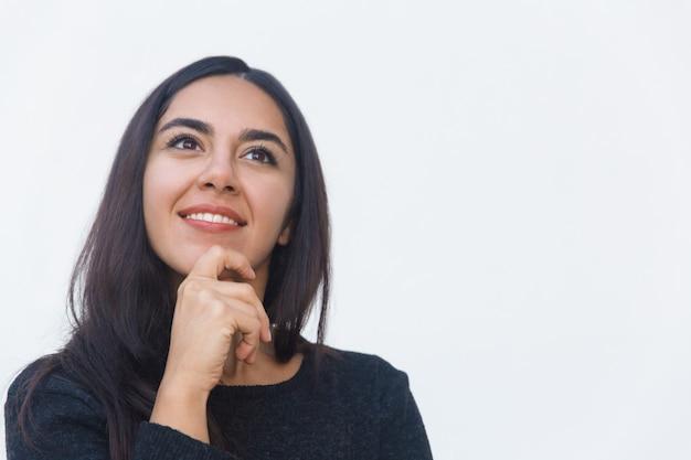 Gelukkige peinzende vrouwelijke klant wat betreft kin
