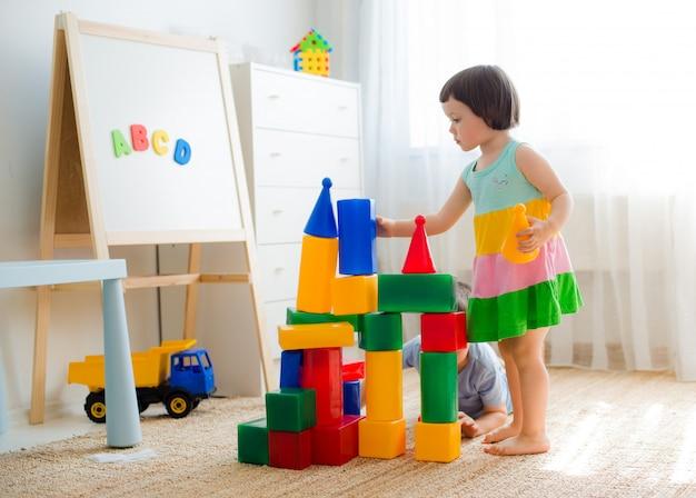 Gelukkige peuterkinderen spelen met stuk speelgoed blokken.