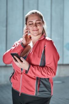 Gelukkige plus size vrouw in koptelefoon met smartphone en muziek luisteren met gesloten ogen