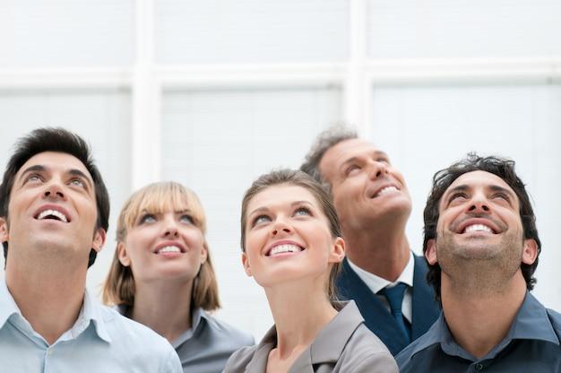 Gelukkige positieve bedrijfsgroep die met dromende uitdrukking omhoog kijkt