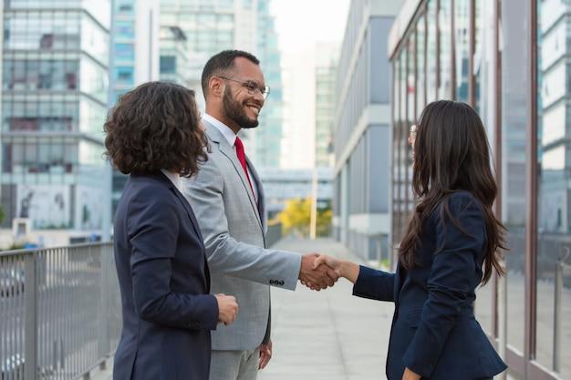 Gelukkige positieve bedrijfsmensen die buiten samenkomen