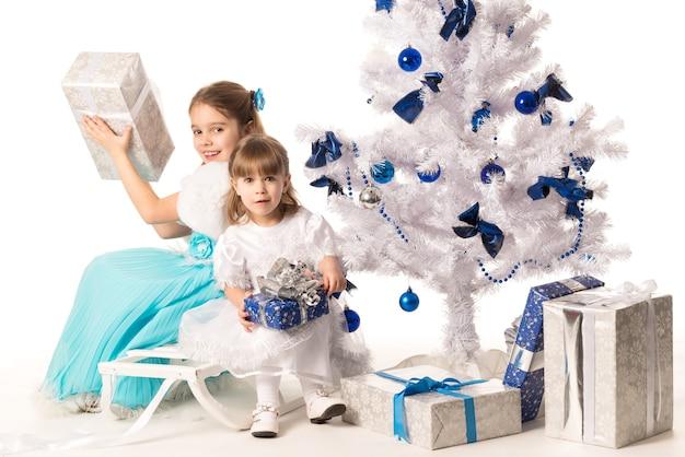 Gelukkige positieve kleine meisjeszusters die giftdozen houden terwijl zij dichtbij een witte kunstmatige kerstboom zitten
