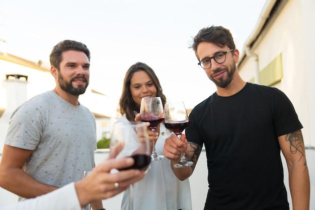 Gelukkige positieve mensen die wijn roosteren
