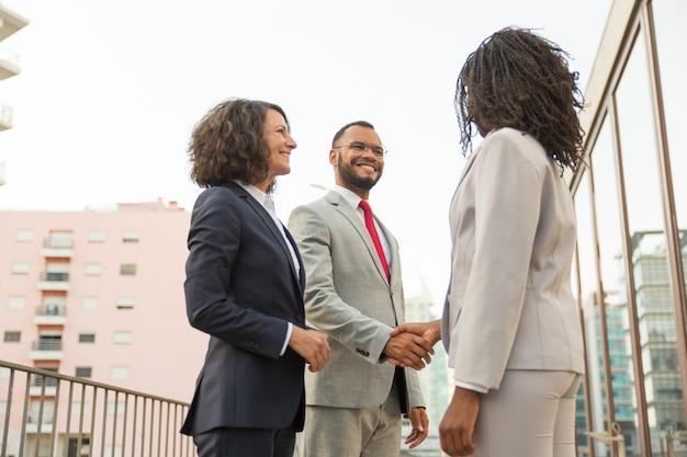 Gelukkige positieve partners die dichtbij bureau samenkomen