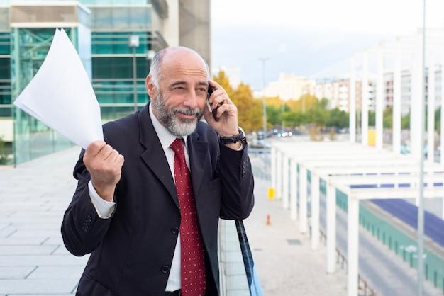Gelukkige positieve rijpe zakenman die overeenkomst bespreekt