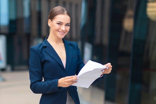 Gelukkige positieve succesvolle mooie vrouw met documenten