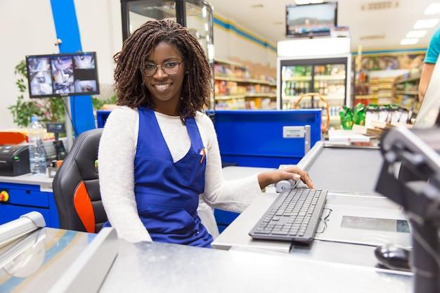 Gelukkige positieve vrouwelijke kassier die in kruidenierswinkelopslag werken