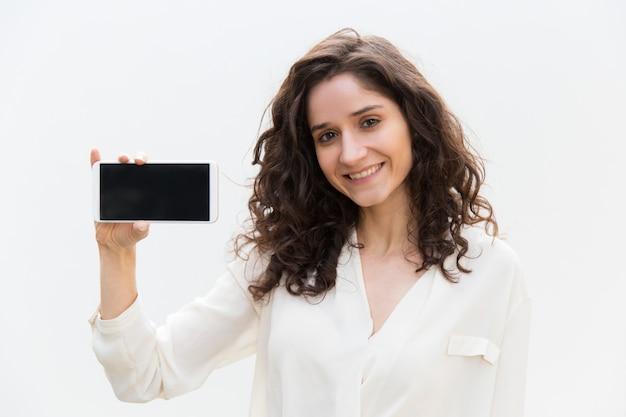 Gelukkige positieve vrouwelijke smartphonegebruiker die het lege scherm toont