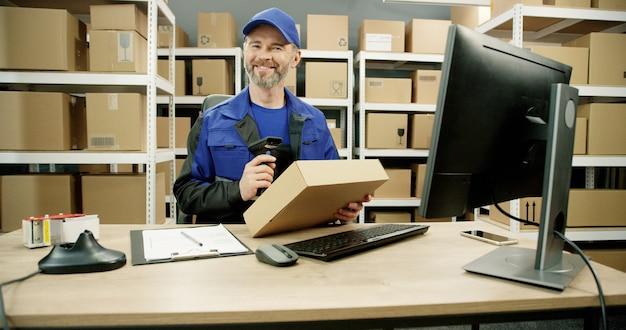 Gelukkige postbode in het eenvormige werken bij computer in postkantooropslag met pakketten.