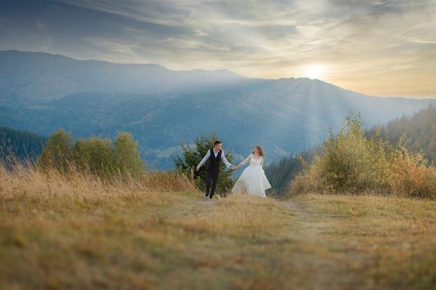 Gelukkige prachtige bruid en stijlvolle bruidegom rennen en plezier, bruidspaar, luxe ceremonie in de bergen met prachtig uitzicht
