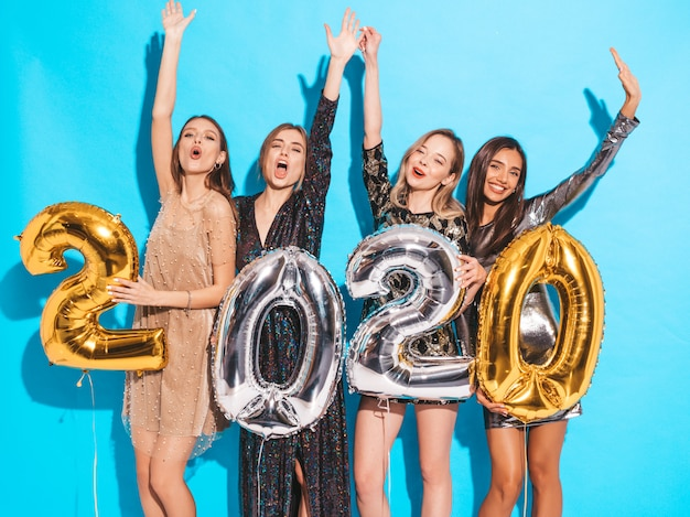 Gelukkige prachtige meisjes in stijlvolle sexy feestjurken met gouden en zilveren 2020-ballonnen
