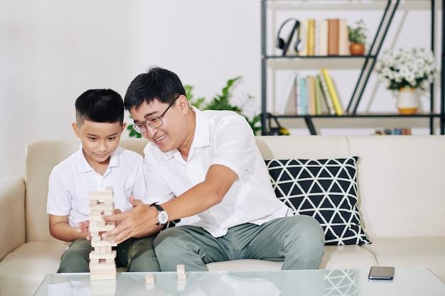 Gelukkige preteenjongen en zijn glimlachende vader bouwen toren uit houten blokken tijdens thuisblijven vanwege coronavirus pandemie