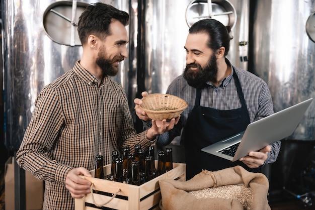 Gelukkige professionele brouwers die de mout inspecteren.